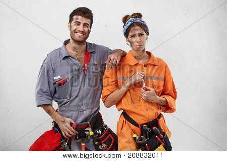 Smiling Male Carpenter Tries To Encourage His Female Colleague Who Has Upset And Tired Expression, B