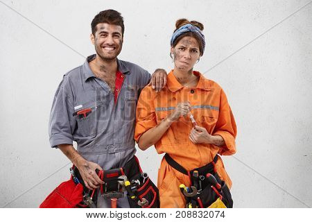 Tired Female Carpenter In Orange Uniform, Holds Screwdriver And Male Colleague With Happy Expression