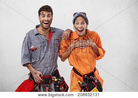 Excited Female And Male Plumbers Don`t Believe Their Eyes, Look With Widely Opened Mouthes In Camera