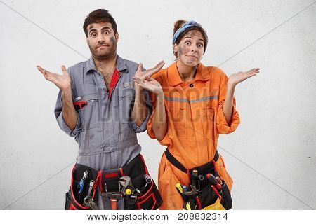 Puzzled Female And Male Plumbers Can`t Understand Where Breakage Is, Shrug Shoulders In Bewilderment