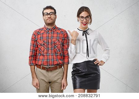 Horizontal Portrait Of Smiling Pretty Woman Looks Happily, Indicates On Male Bearded Nerd In Spectac