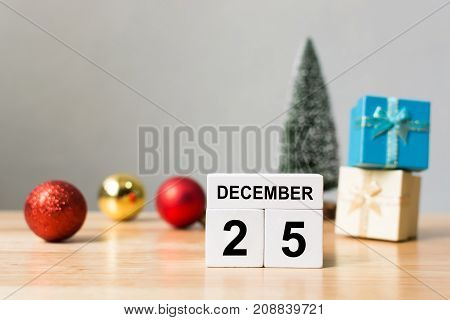 Wooden block calender 25th December and christmas decoration object on wood table with white wall background Happy Christmas holiday celebration concept Copy space your text
