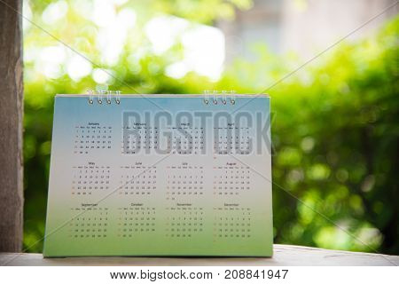 Green calendar on bokeh background planning concept.