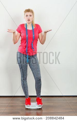 Woman Wearing Sportswear Standing On Weight Machine