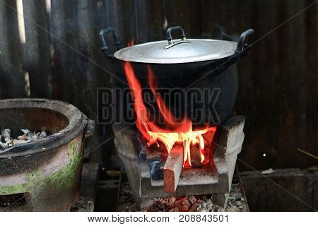 Old Metal Pot On Earthen Stove With Hot Fire Flame