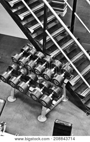 Small dumbels on the gym near stairs. Fit lifestyle concept.