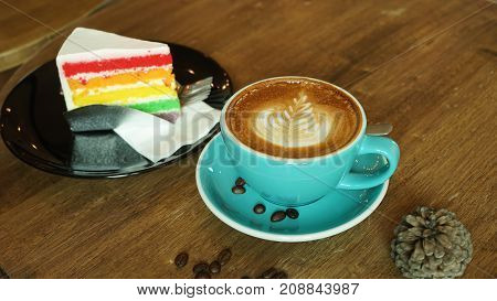 Hot coffee with rainbow cheesecake latte mocha espresso cappuccino with heart shape foam in green cup coffee shop wooden tabvle and coffee bean