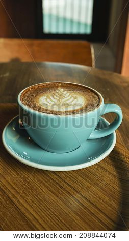 Hot coffee latte mocha espresso cappuccino with heart shape foam in green cup coffee shop wooden tabvle and coffee bean
