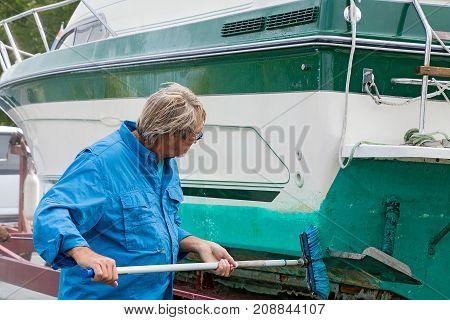 Caucasian man washing boat dirty boat hull with long handle brush