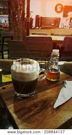 hot coffee with milk foam and syrup glass bottle on wooden tray and coffee bean/hot coffee