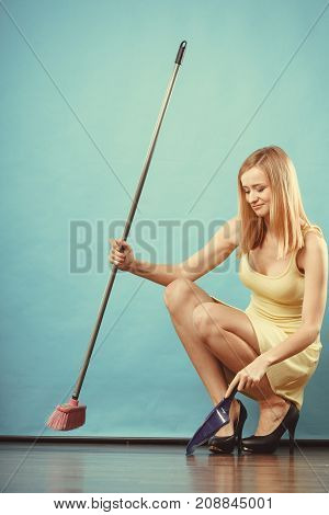 Cleanup housework concept. Elegant sensual woman sweeping wooden floor with broom.