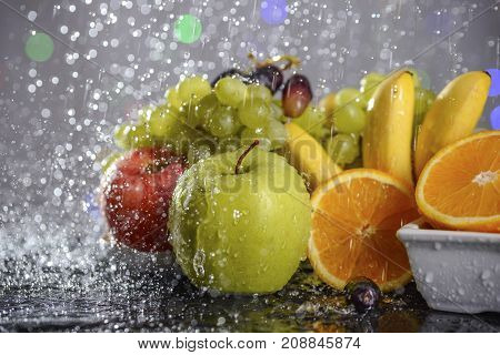 Festive still-life from fresh colorful fruits in drops and splashes of falling water