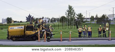 Saint Quentin, New Brunswick - August 17, 2011 - Wide view of a work crew of city workers standing alongside a road being groomed for paving with houses and greenery in the background, near Bathurst, NB on a bright sunny day with blue skies.