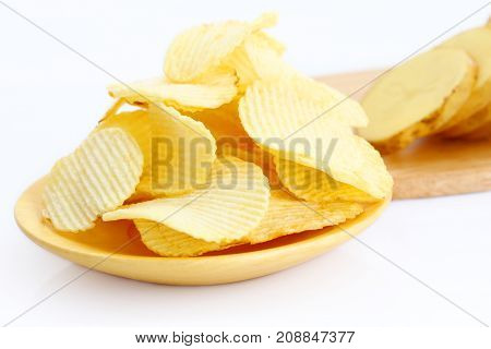 Group of potato chips isolated on wooden plate over white background.