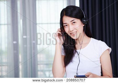 Woman In Headphones Listening To Music From Smartphone With Window Background