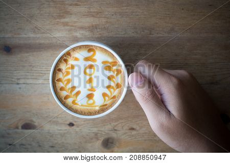 hot coffee with foam milk art 2018 on wooden table latte art coffee