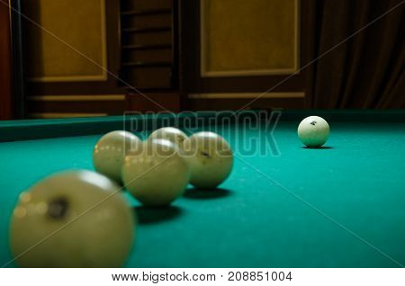 Russian billiards white balls, yellow cue ball on a large table with green cloth