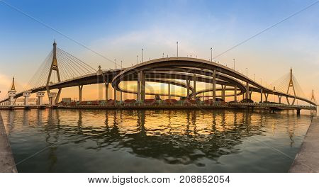 Sunset over double suspension bridge with highway interchanged river front