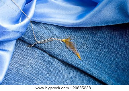 Dense Blue Denim Fabric, Smooth Sky-blue Silk And Gold Chain With Pendant Feather
