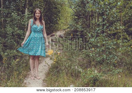 Young Woman In Romantic Blue Dress With Yellow Flowers In The Mountains