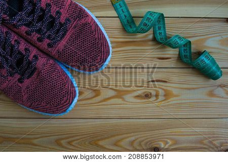 Sneakers And Centimeter Top View. Healthy And Active Lifestyles. Wooden Background.