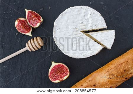 Triangular appetizing piece of camembert cheese and a formed cheese, pieces of figs in honey and a wooden spoon for honey and browned baguette on a graphite black background.