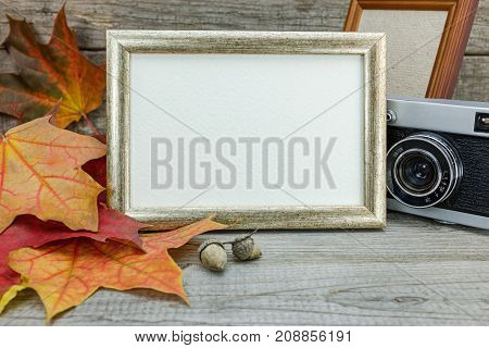 Old Retro Camera And Empty Photo Frames On Grunge Wooden Background With Colorful Maple Leaves