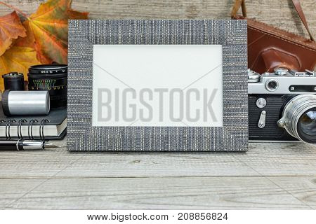 Vintage Camera, Films, Lenses And Frame On Grunge Wooden Background With Colorful Dried Leaves