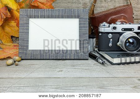 Retro Camera And Photo Frame On Grey Wooden Background With Fallen Leaves
