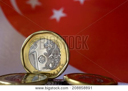 Singaporean dollar coins with flag as background.