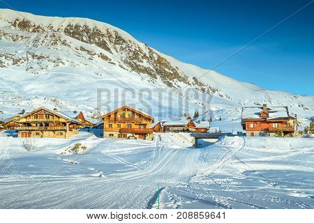 Wonderful winter landscape with wooden chalets and ski slopes in French Alps Alpe D Huez France Europe
