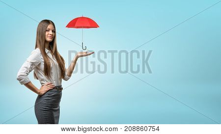 A young businesswoman supports a small open red umbrella on his open palm. Insurance agent. Data protection services. Corporate consulting.