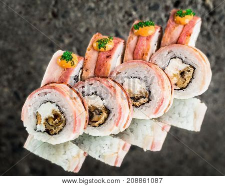 Bacon wraped roll with crisp mussels over concrete background