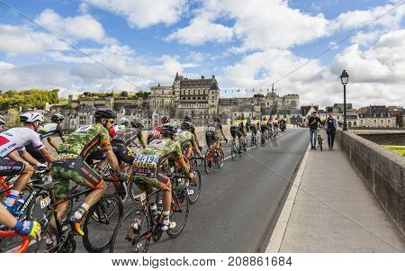 AmboiseFrance - October 82017: The peloton passing on the bridge in front of Amboise Castle during the Paris-Tours road cycling race.