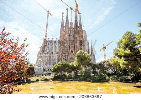 BARCELONA, SPAIN - August 16, 2017: View from the park on the famous unfinished Roman Catholic church Sagrada Familia in Barcelona, designed by Catalan architect Antoni Gaudi
