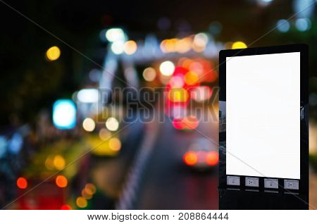 mock up blank advertising billboard with copy space for your text message or media and content with blurred image of traffic light in the city at nigh commercial marketing and advertising concept