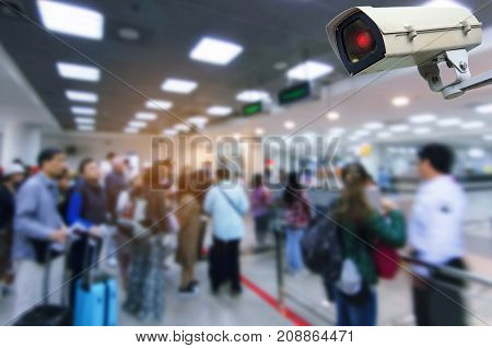 CCTV security camera system operating with blurred view of people queue at immigration control in airport surveillance security and safety technology concept