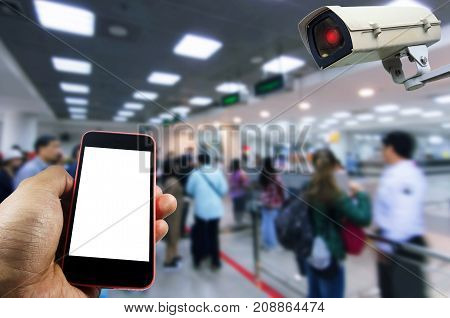 hand using mobile phone with blank screen and security camera system operating with people queue at immigration control in airport internet surveillance security and safety technology concept