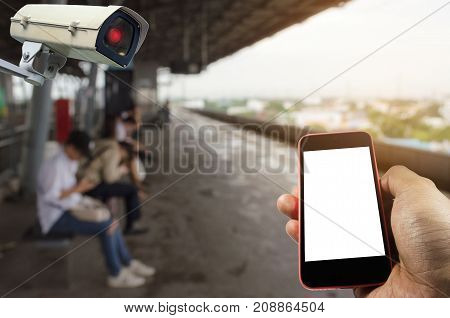 hand using mobile phone with blank screen and security camera system operating with blurred view of people waiting sky train at station internet surveillance security and safety technology concept