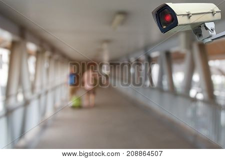 CCTV security camera system operating with blurred view of people with luggage at airport surveillance security and safety technology concept