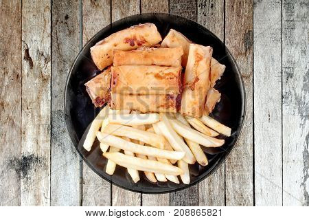 Deep fried spring roll as flour sheet wrap fried vermicelli and sliced cabbage in roll bar to deep fried call as Por Peai J in Thai served with French fries for Chinese Vegetable festival food