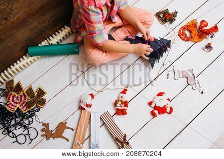 Christmas preparation. Art decoration process. Favorite time of year, unrecognizable girl artist on white background, creative presents creation top view, festivity concept