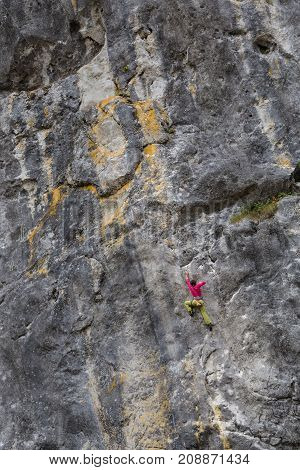 Strong girl climbs on a rock wall, doing sports climbing in nature.