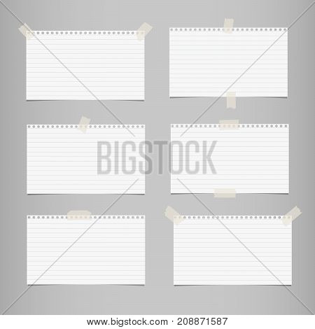 White striped note, notebook paper for message or text stuck with sticky tape on gray background