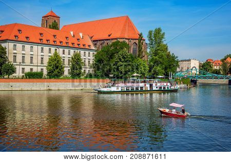 Wroclaw/Poland- August 18, 2017: View of large and small touristic boats on Odra River, old Catholic Church of Saint Mary on the Sand, Tumski bridge, green trees and blue sky.