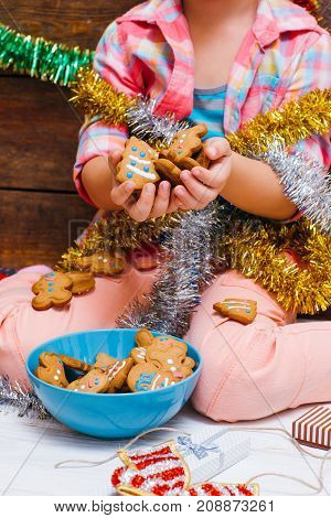 Sweet Christmas. Child dream life. Unrecognizable girl with many gingerbread. Festive mood on New Year, food concept