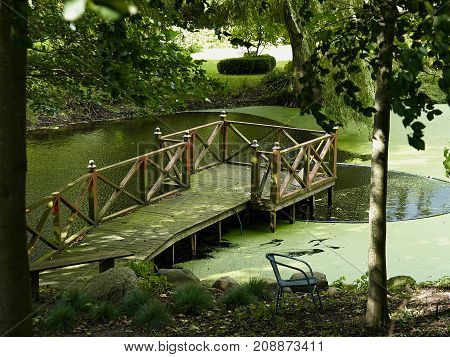 Small back yard paradise wooden deck on a relaxing green pond in a garden