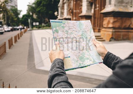 A picture of a city map. It is hold by one young tourist that bought this map some time ago. The interesting and unusual way for those days to try to find some location on the paper map. Close up. Cut view