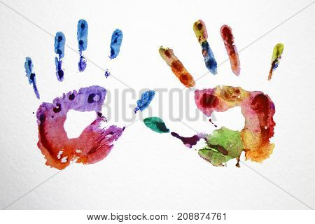 watercolor multicolored prints of hands on a white sheet of paper