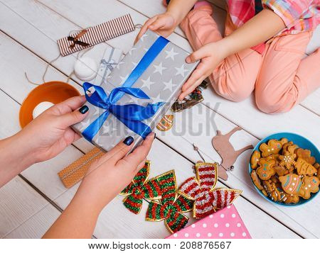 Family love on New Year's day. Christmas miracle. Unrecognizable women together on wooden background top view. Favorite time, festive decorations, dream gift